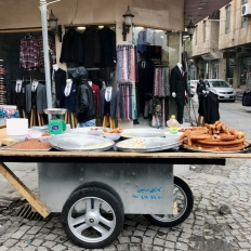 On the streets, a vendor's cart with the Kurdish version of Spanish Churros?...